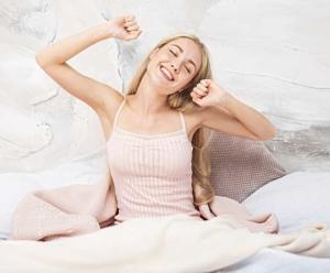 Frau wacht auf und streckt sich im Bett