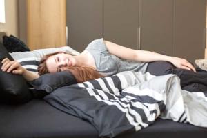 Frau liegt in bequemem Bett