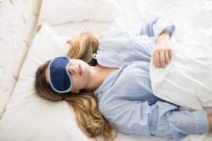 Frau schläft mit Schlafmaske im Bett