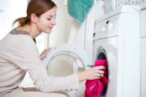 Frau nimmt Wäsche aus der Maschine