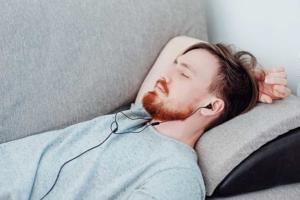 Schlafender Mann mit Kopfhörern hört Geräusche zum Einschlafen