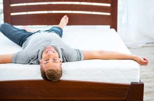 Mann liegt auf einer Matratze und lächelt