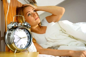 Frau kann nicht schlafen und liegt wach im Bett