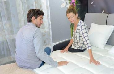 Paar testet den Härtegrad einer Matratze