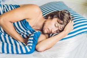 Mann liegt im Bett und befindet sich im Tiefschlaf